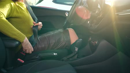 kézi : Woman fastening car safety seat belt while sitting inside of vehicle before driving