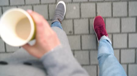 paving : Top view of male and female legs strolling along the sidewalk. Woman drinking coffee Stock Footage