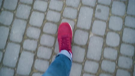 мощение : Top view of mens legs in red sneakers walking along the sidewalk