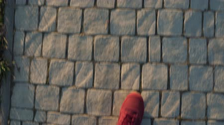 šedé pozadí : Top view of mens legs in red sneakers walking along the sidewalk