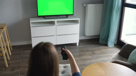 zatáčka : Woman is sitting in a chair, watching TV with a green screen, switching channels with a remote control. Chroma key. Indoors