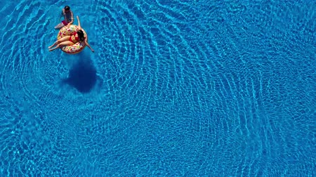 plavat : Aerial view of couple having fun in the pool, man is swimming and a woman is lying on an inflatable donut Dostupné videozáznamy