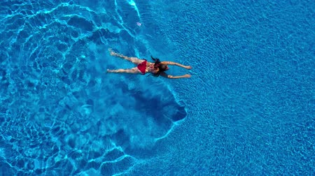 relaks : View from the top as a woman in a red swimsuit swims in the pool
