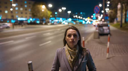 noc : Timelapse of woman standing still on crowded evening street while a blur of fast moving cars move behind her