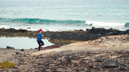 perspektif : Woman runs along the stony shore of the ocean. Healthy active lifestyle