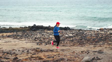 stony : Woman runs along the stony shore of the ocean. Healthy active lifestyle. Slow motion Stock Footage