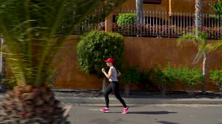 perspektif : Woman runs down the street among the palm trees. Healthy active lifestyle