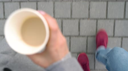 grãos de café : Top view of male and female legs strolling along the sidewalk. Woman drinking coffee Vídeos