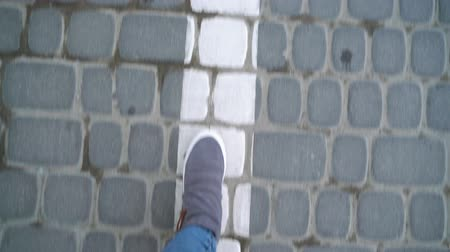 šedé pozadí : Top view of female legs in gray sneakers walking on the sidewalk