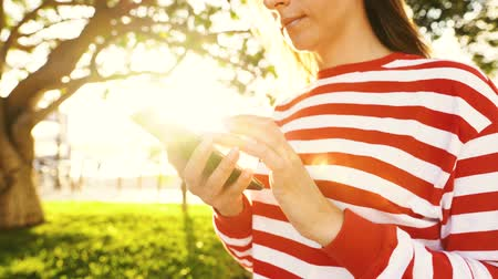 navegar : Woman using smartphone outdoors against the setting sun Stock Footage
