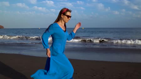 praia : Woman in a blue dress runs along a black volcanic beach. Slow motion