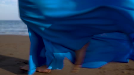 praia : Legs of a woman in beautiful blue dress walking along a black volcanic beach
