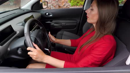 отчаянный : Woman is angry and beating her hands on the steering wheel, because her car broke down