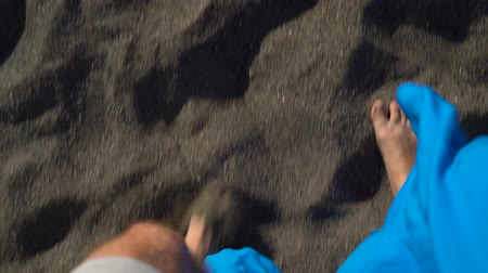 молодой человек : Top view of couple strolling together at the black volcanic sand at ocean beach Стоковые видеозаписи