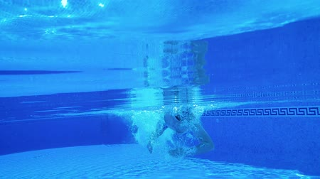 flutuador : Underwater shooting as a man swims under the water