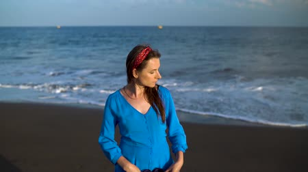 sziget : Portrait of a woman in a beautiful blue dress on a black volcanic beach. Slow motion