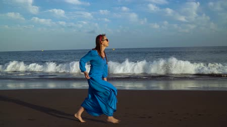 sziget : Woman in a blue dress runs along a black volcanic beach. Slow motion