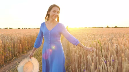 vychovávat : Beautiful woman in a blue dress and hat walking through a wheat field at sunset. Freedom concept. Wheat field in sunset