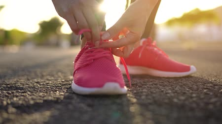 waga : Close up of woman tying shoe laces and running along the palm avenue at sunset. Slow motion