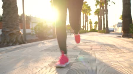 recreatie : Close up of woman running along the palm avenue at sunset