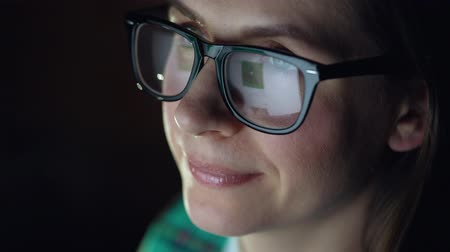 очки : Woman in glasses looking on the monitor and surfing Internet. The monitor screen is reflected in the glasses Стоковые видеозаписи