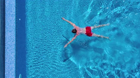 lidské tělo : Aerial view of man in red shorts swims and and climbs out of the pool Dostupné videozáznamy