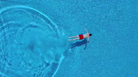 relaks : View from the top as a man dives into the pool and swims under the water Wideo
