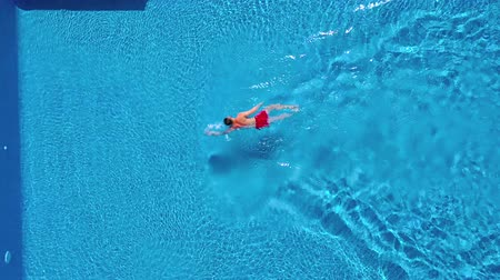 plavat : Aerial view of man in red shorts swims in the pool