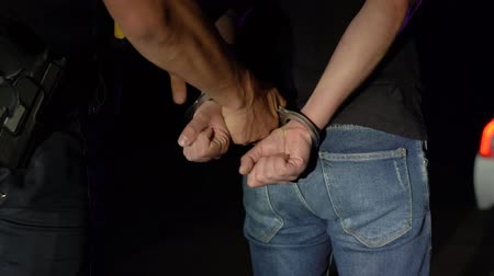 noc : Police officer puts handcuffs on arrested man at night and leads him to a police car