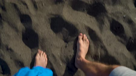 relaks : Top view of couple strolling together at the black volcanic sand at ocean beach Wideo