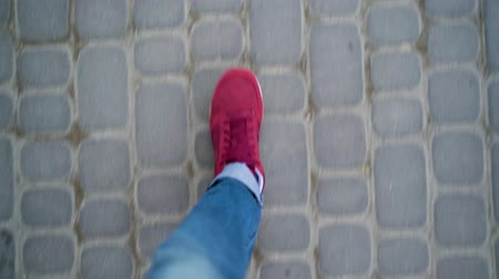 adam : Top view of mens legs in red sneakers walking along the sidewalk
