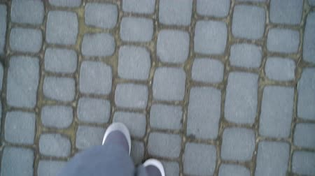 cipő : Top view of female legs in gray sneakers walking on the sidewalk