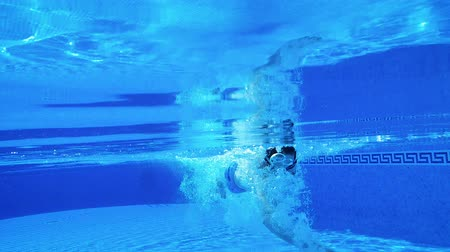 bolha : Underwater shooting as a man swims under the water in the pool. Slow motion