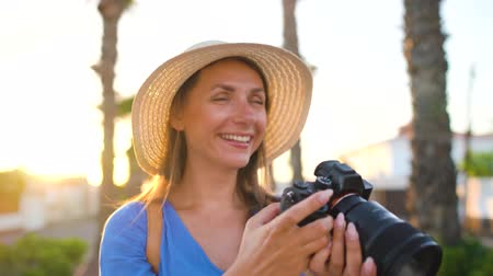 aparat : Photographer tourist woman taking photos with camera in a beautiful tropical landscape at sunset