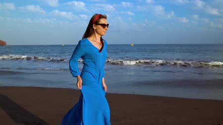kanári : Woman in a blue dress runs along a black volcanic beach