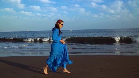 praia : Woman in a blue dress runs along a black volcanic beach