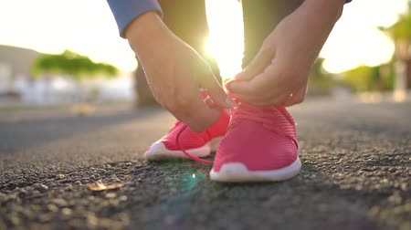кроссовки : Close up of woman tying shoe laces and running along the palm avenue at sunset