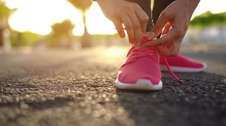 ağaç gövdesi : Close up of woman tying shoe laces and running along the palm avenue at sunset. Slow motion