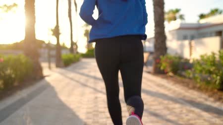 kardio : Close up of woman tying shoe laces and running along the palm avenue at sunset. Back view. Filmed at different speeds - slow motion and normal