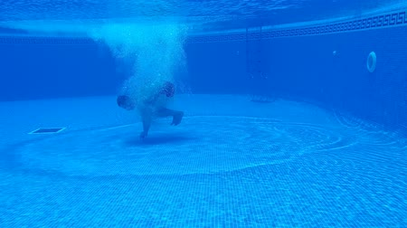 spat : Underwater shooting as a man dives like a bomb into the pool and swims under the water. Slow motion Stockvideo
