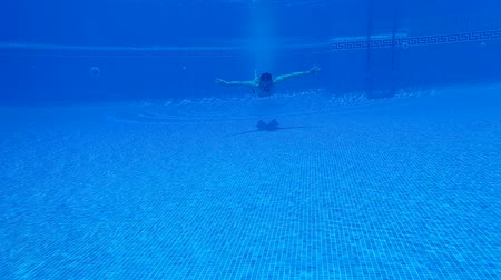 plavat : Underwater shooting as a man dives into the pool and swims under the water