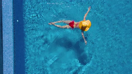 plavat : View from the top as a woman in a red swimsuit and a big yellow hat swims in the pool