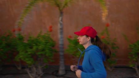 perspektif : Woman runs down the street among the tropical alley. Healthy active lifestyle Stok Video