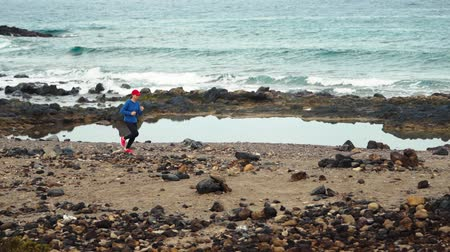 perspektif : Woman runs along the stony shore of the ocean. Healthy active lifestyle. Slow motion Stok Video