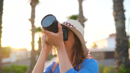 фотографий : Photographer tourist woman taking photos with camera in a beautiful tropical landscape at sunset