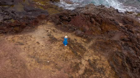pedras : Aerial view of woman in a beautiful blue dress and hat stands on top of a mountain in a conservation area on the shores of the Atlantic Ocean. Tenerife, Canary Islands, Spain