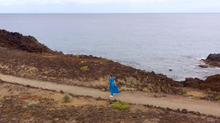 altura : Aerial view of woman in a beautiful blue dress and hat walks through a conservation area on the shores of the Atlantic Ocean. Tenerife, Canary Islands, Spain Stock Footage