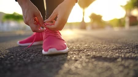 waga : Close up of woman tying shoe laces and running along the palm avenue at sunset