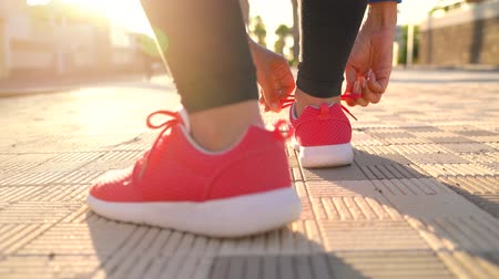 waga : Close up of woman tying shoe laces and running along the palm avenue at sunset. Back view Wideo