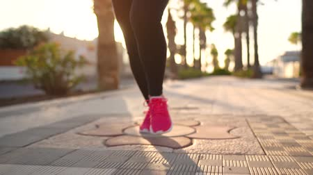 kardio : Close up of legs of a woman running along the palm avenue at sunset. Slow motion